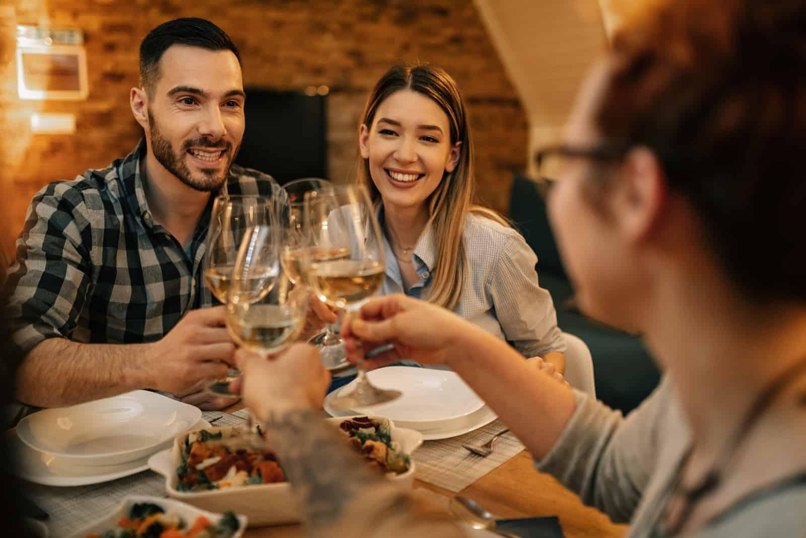 Junges glückliches Paar, das Spaß beim Anstoßen mit Freunden während des Abendessens am Esstisch hat