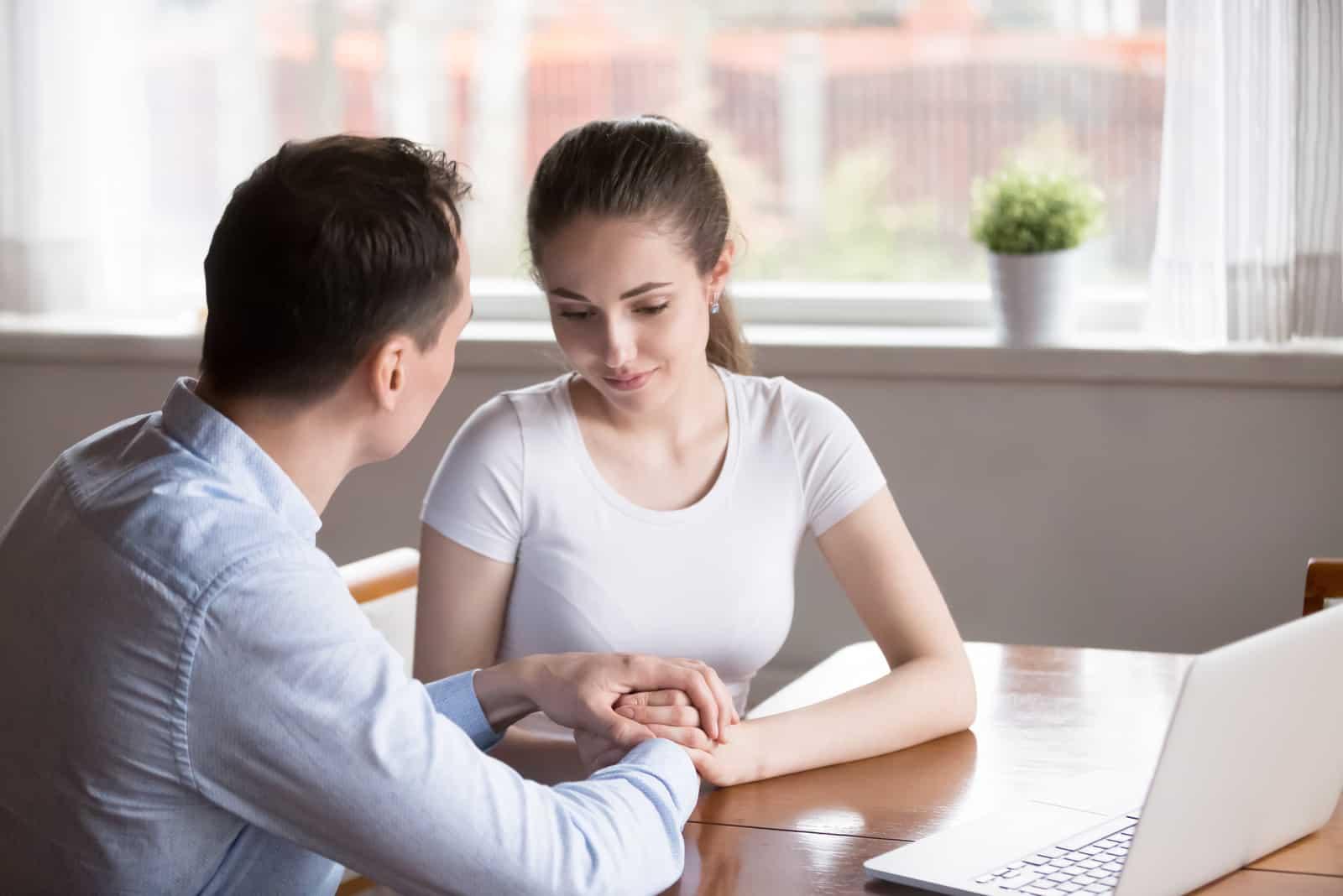 Der Mann tröstet die Frau, als sie am Tisch sitzen