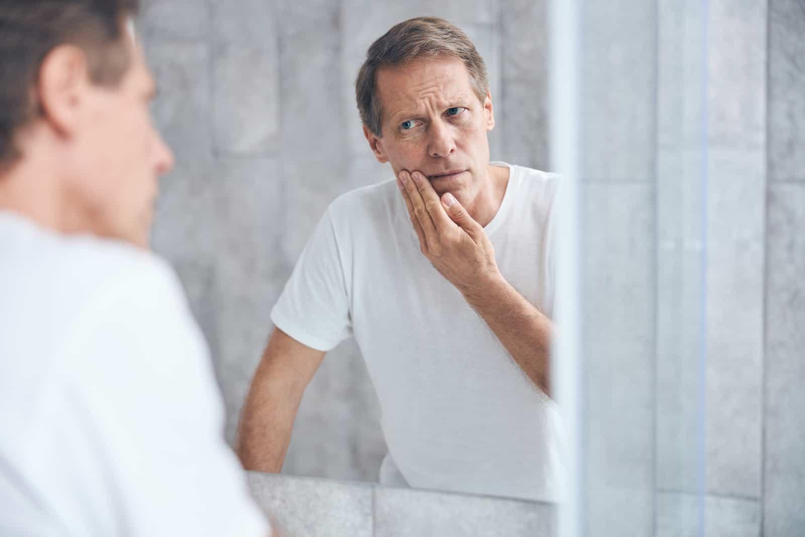 Mann mittleren Alters, der sich im Fenster ansieht