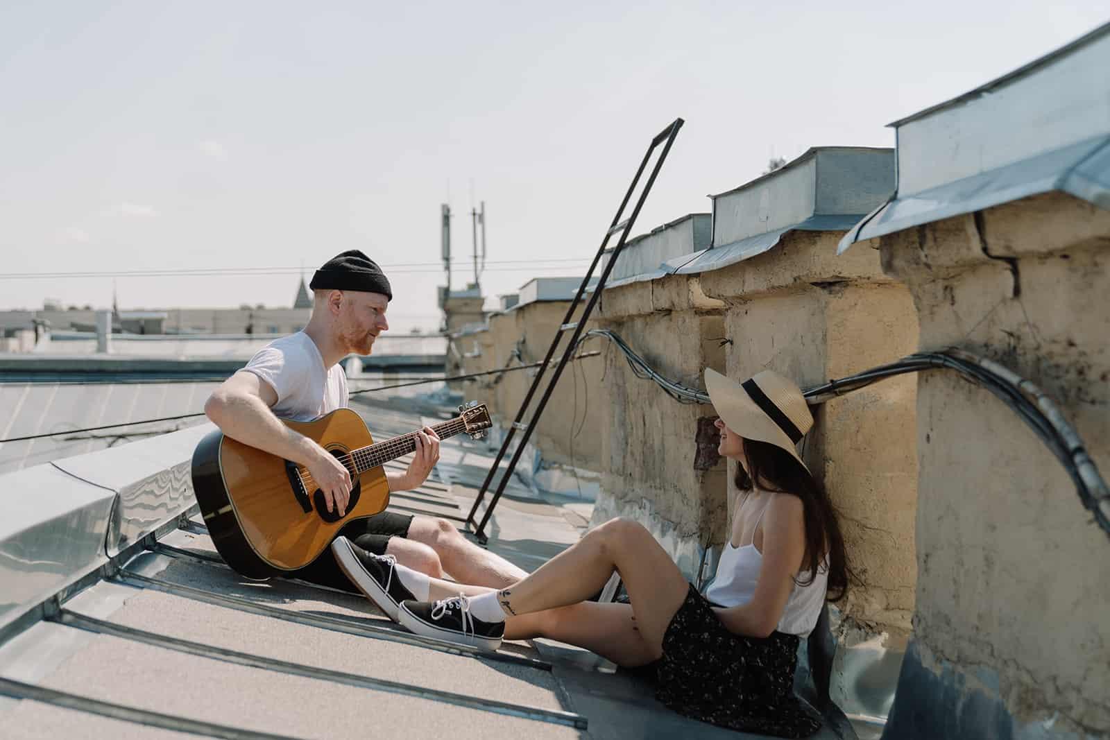 Mann spielt Gitarre für eine Frau auf einem Dach