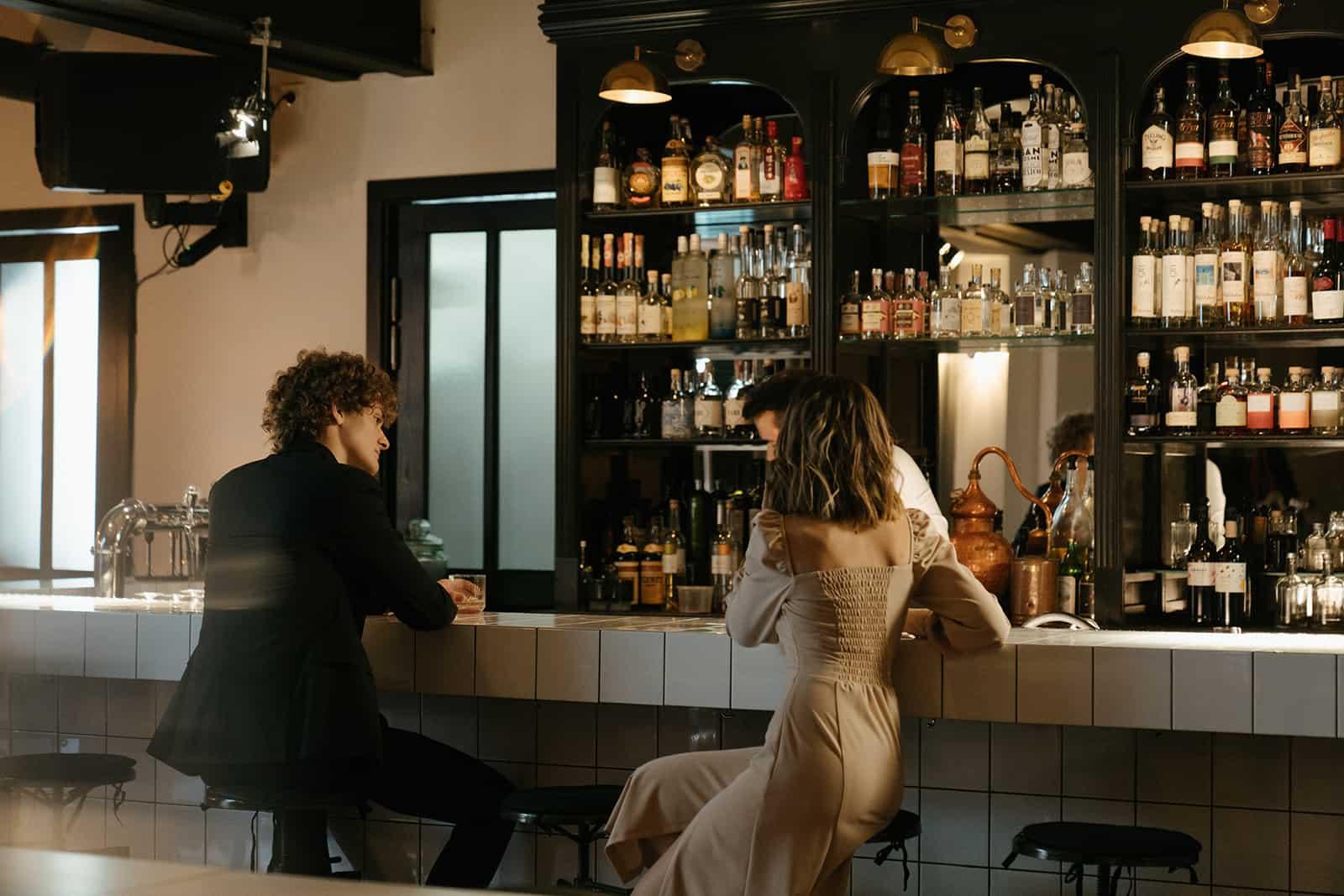 Mann spricht mit einer Frau, die an der Theke sitzt und etwas trinkt