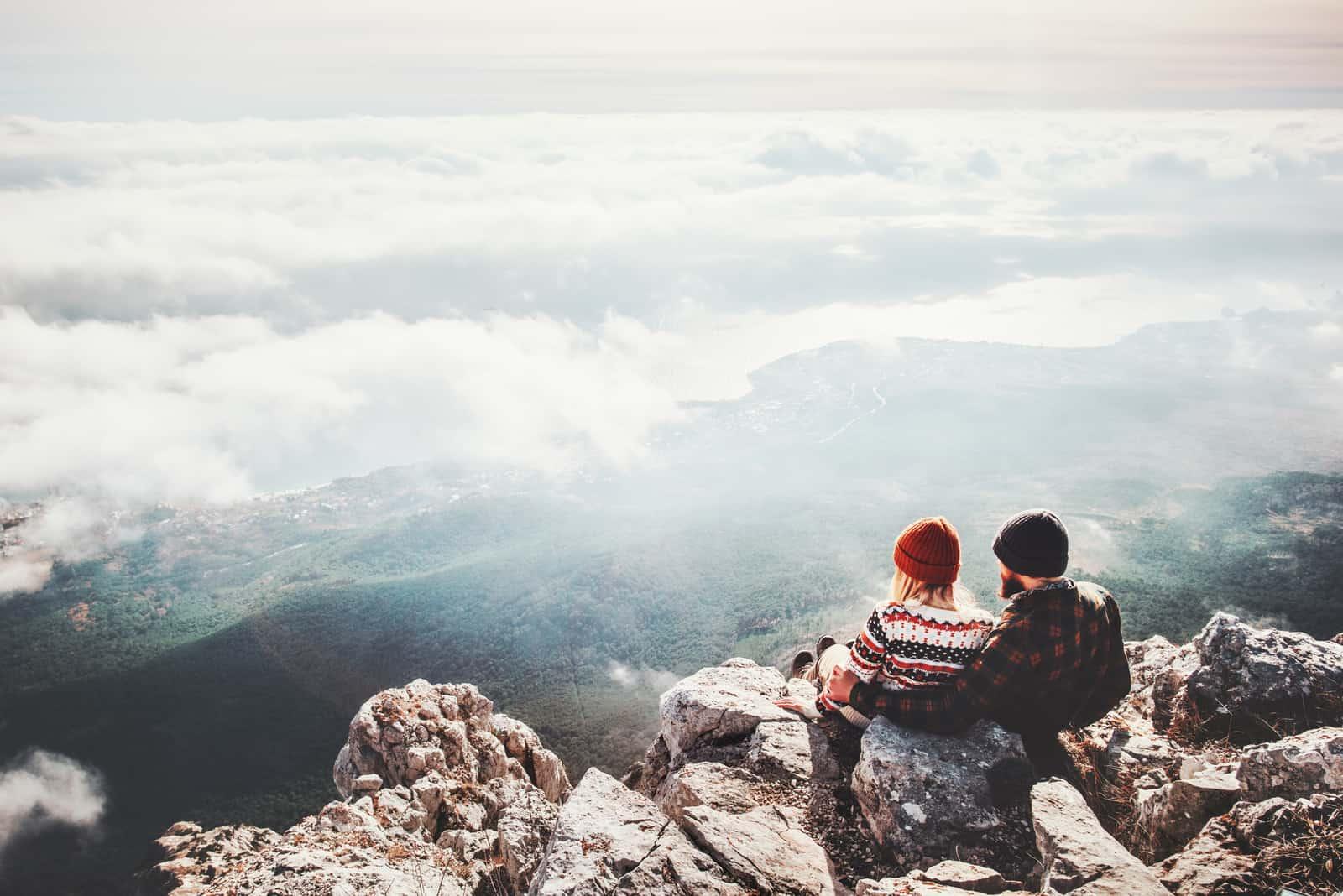 Mann und Frau sitzen auf Klippe entspannend
