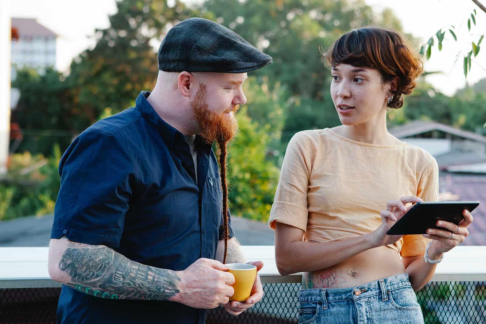 Mann und Frau unterhalten sich auf dem Balkon beim Kaffeetrinken