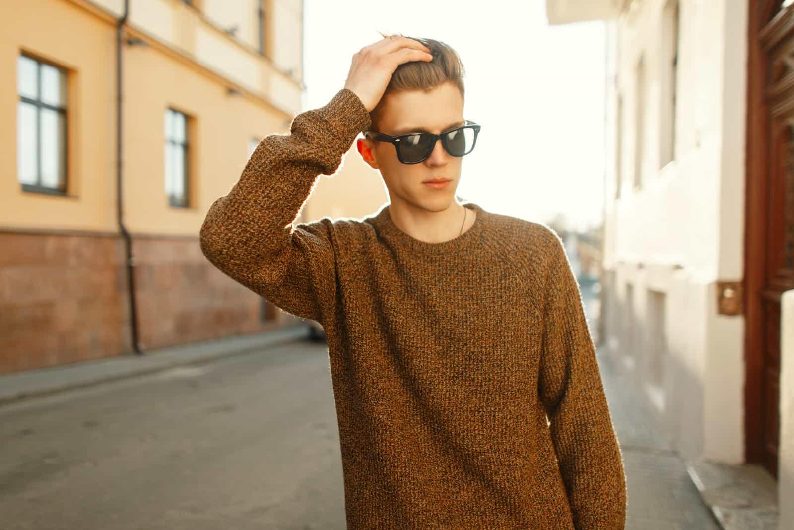 Mannmodell in der stilvollen Sonnenbrille in einem Modepullover, der in der Stadt bei Sonnenuntergang geht