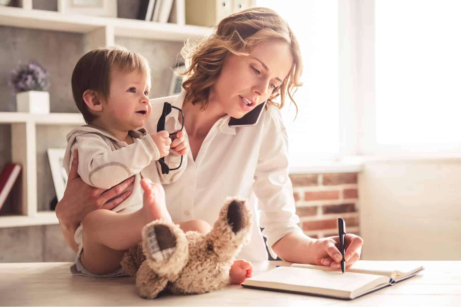 Mutter telefoniert und macht sich Notizen, während sie Zeit mit ihrem süßen Jungen zu Hause verbringt