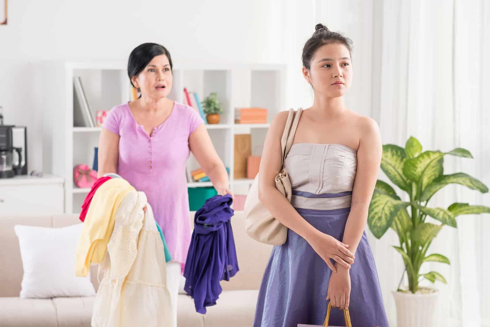 Mutter und Tochter streiten sich, während sie Kleidung in der Hand hält