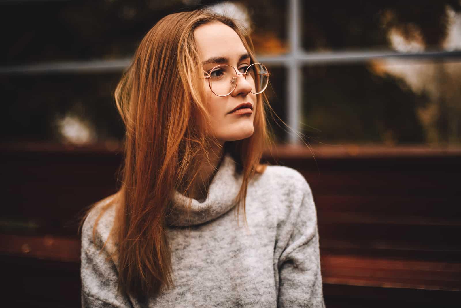 Nahaufnahme der nachdenklichen jungen Frau mit den langen blonden Haaren, die im Park sitzen und denken