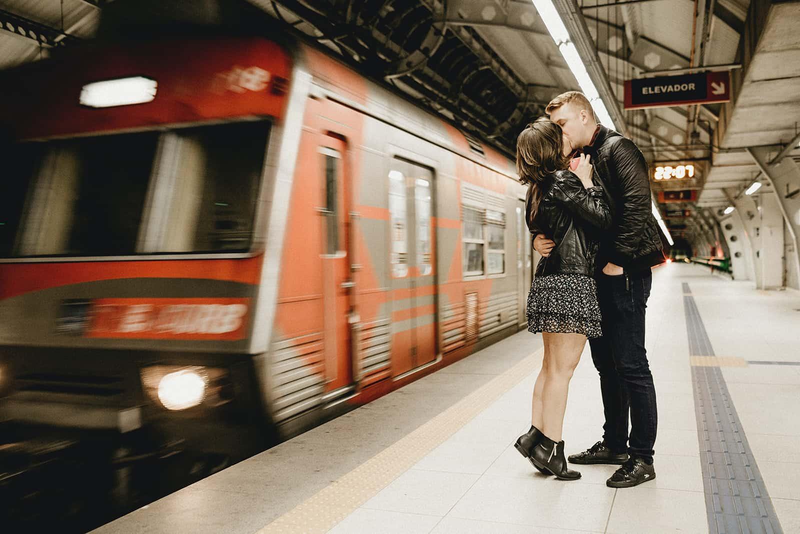 Paar küsst sich in einer U-Bahn, während der Zug neben ihnen vorbeifährt
