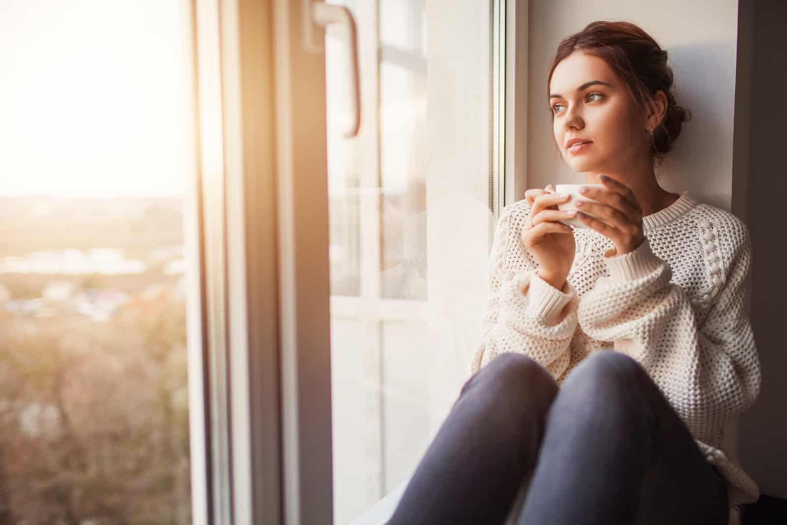 Schöne junge Frau, die Kaffee trinkt