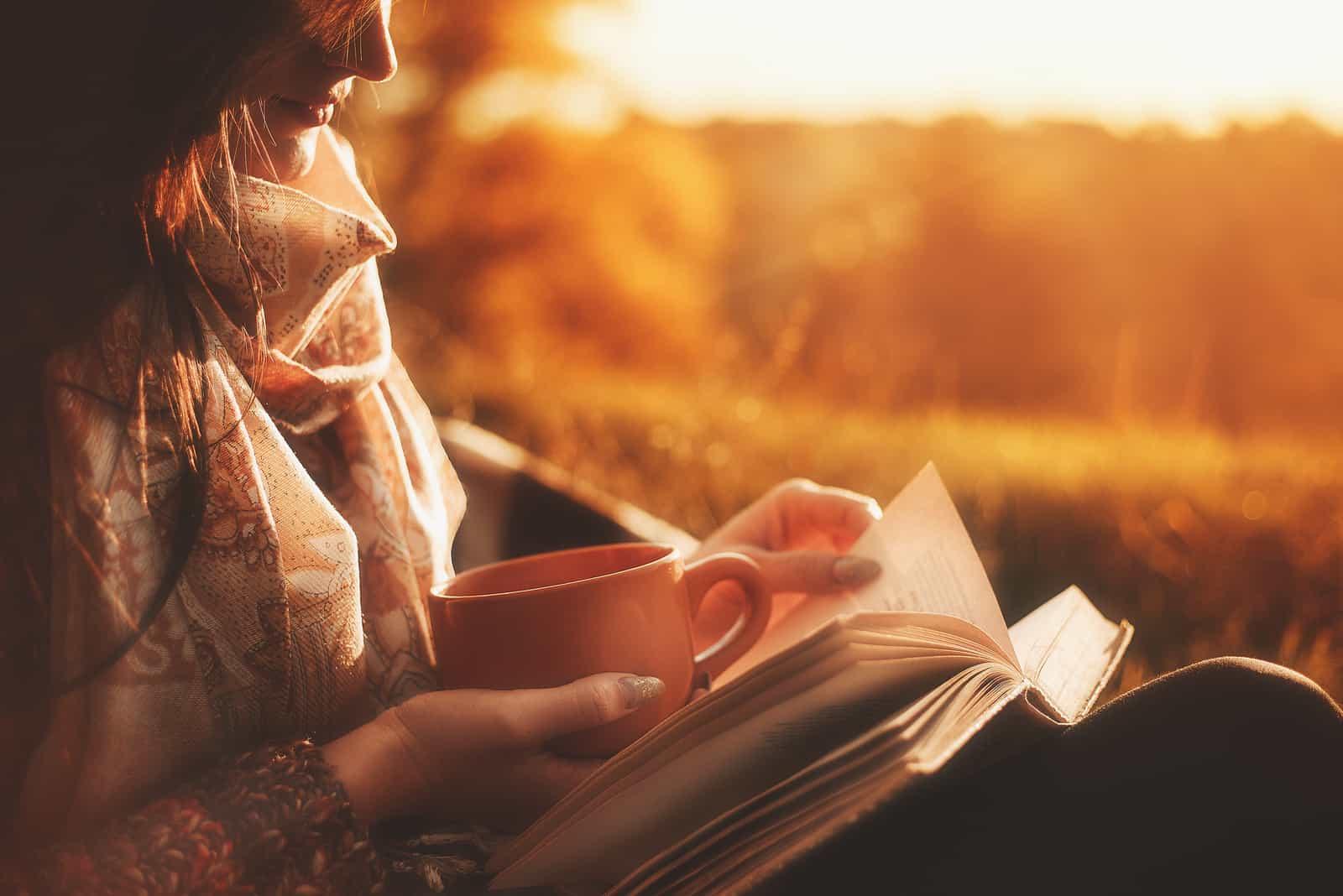 Schönes Mädchen im Herbstwald, das ein Buch liest