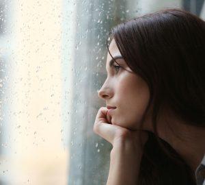 Eine nachdenkliche Frau sitzt und schaut aus dem Fenster