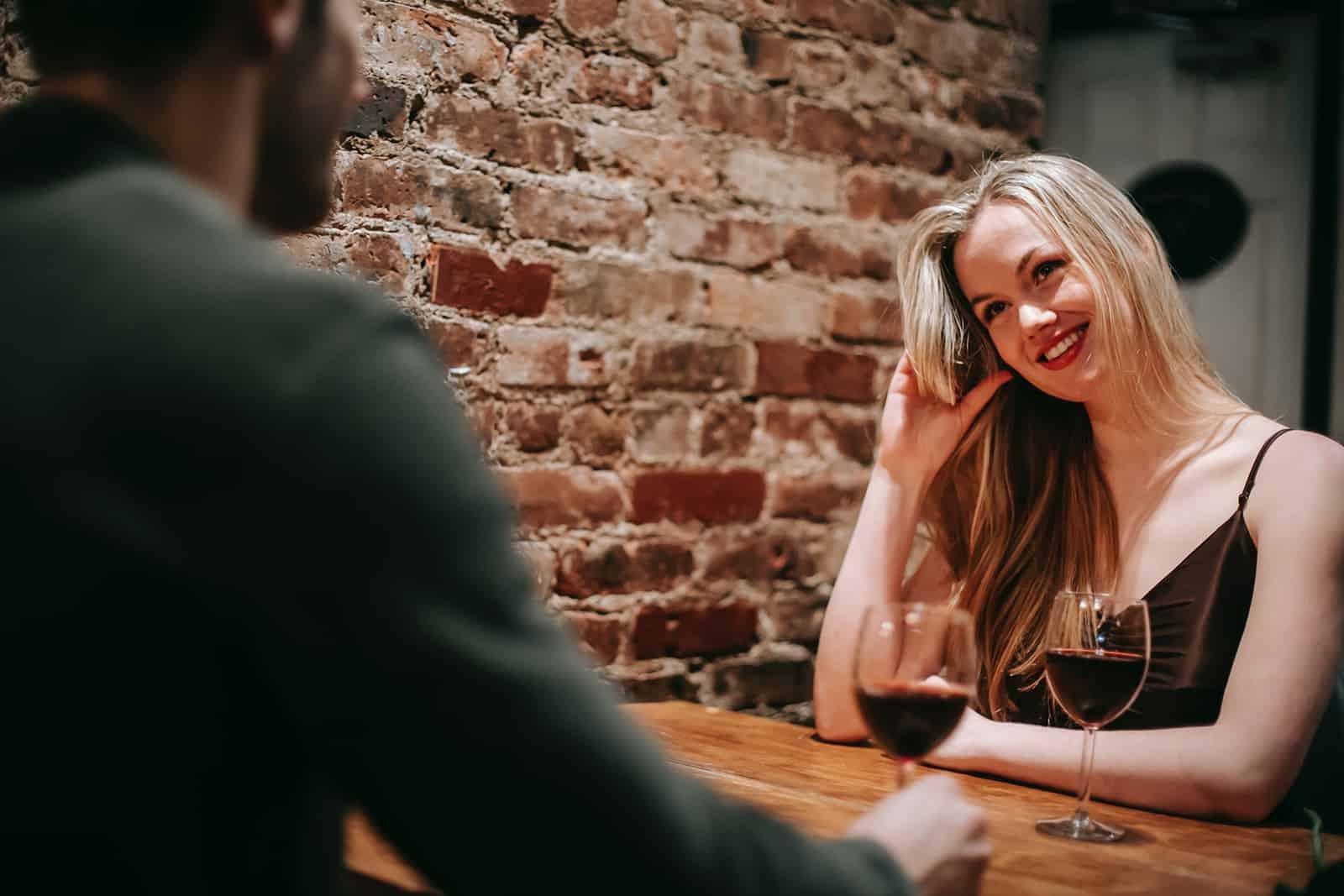 attraktive Frau, die mit einem Mann in einem Restaurant sitzt und zusammen Wein trinkt