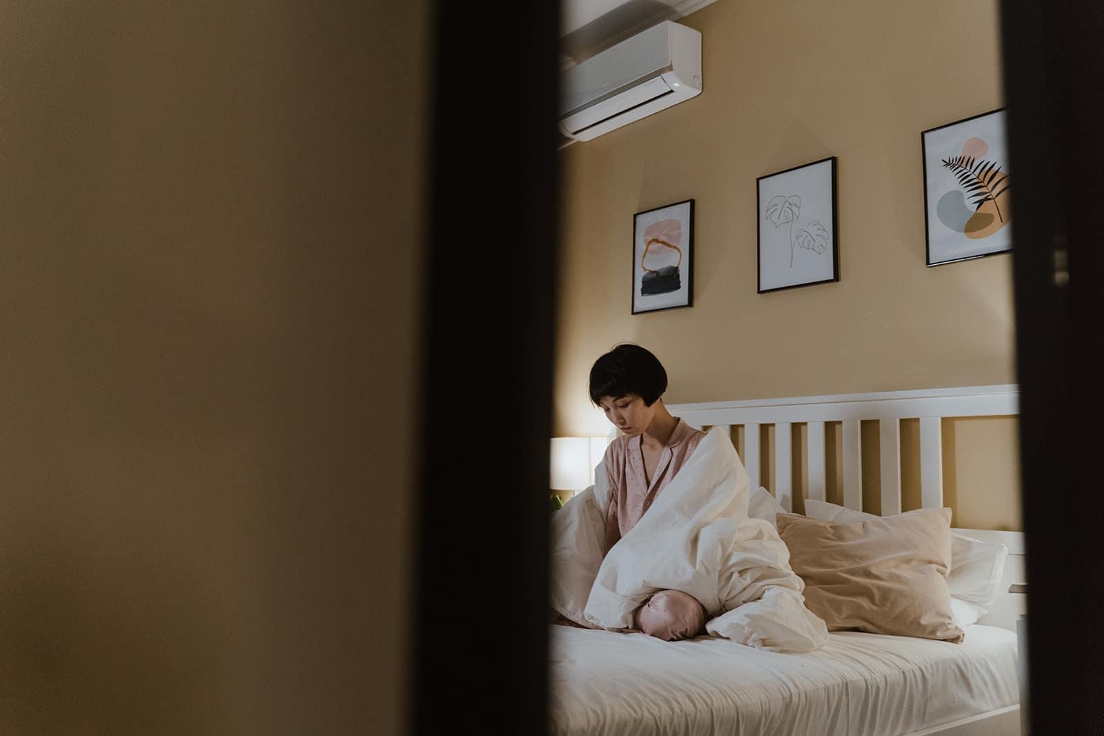 depressive Frau sitzt auf dem Bett mit Decke bedeckt