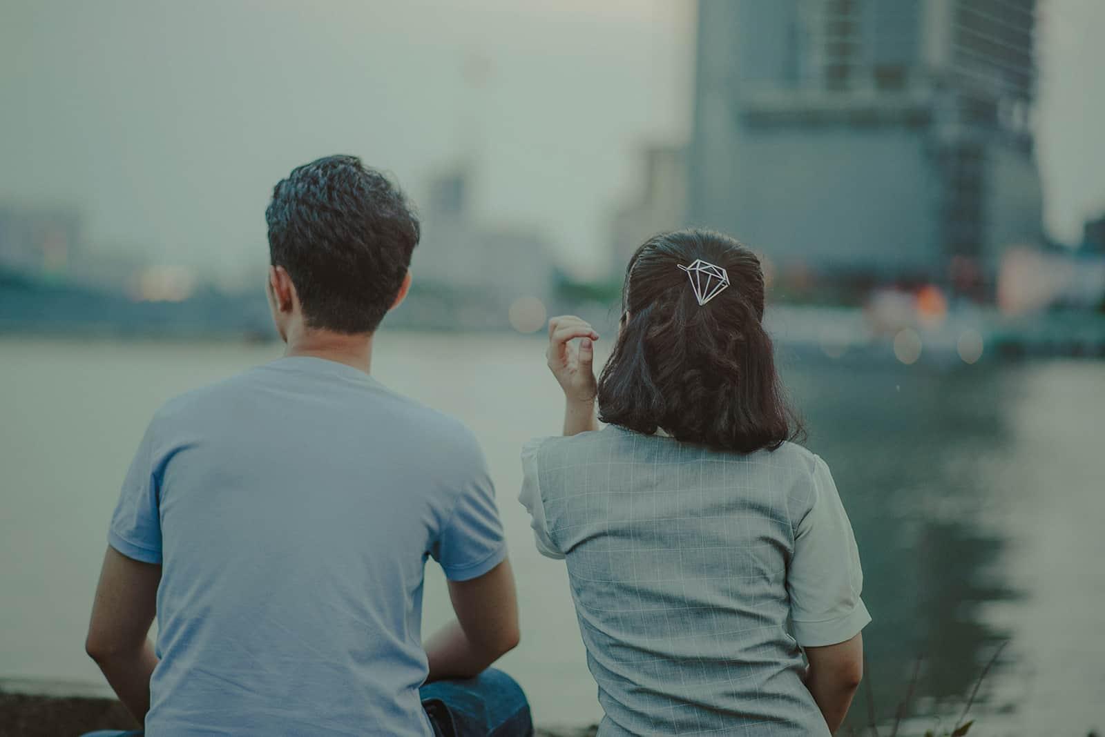 ein Mann und eine Frau sitzen zusammen im Freien gegenüber dem Gewässer