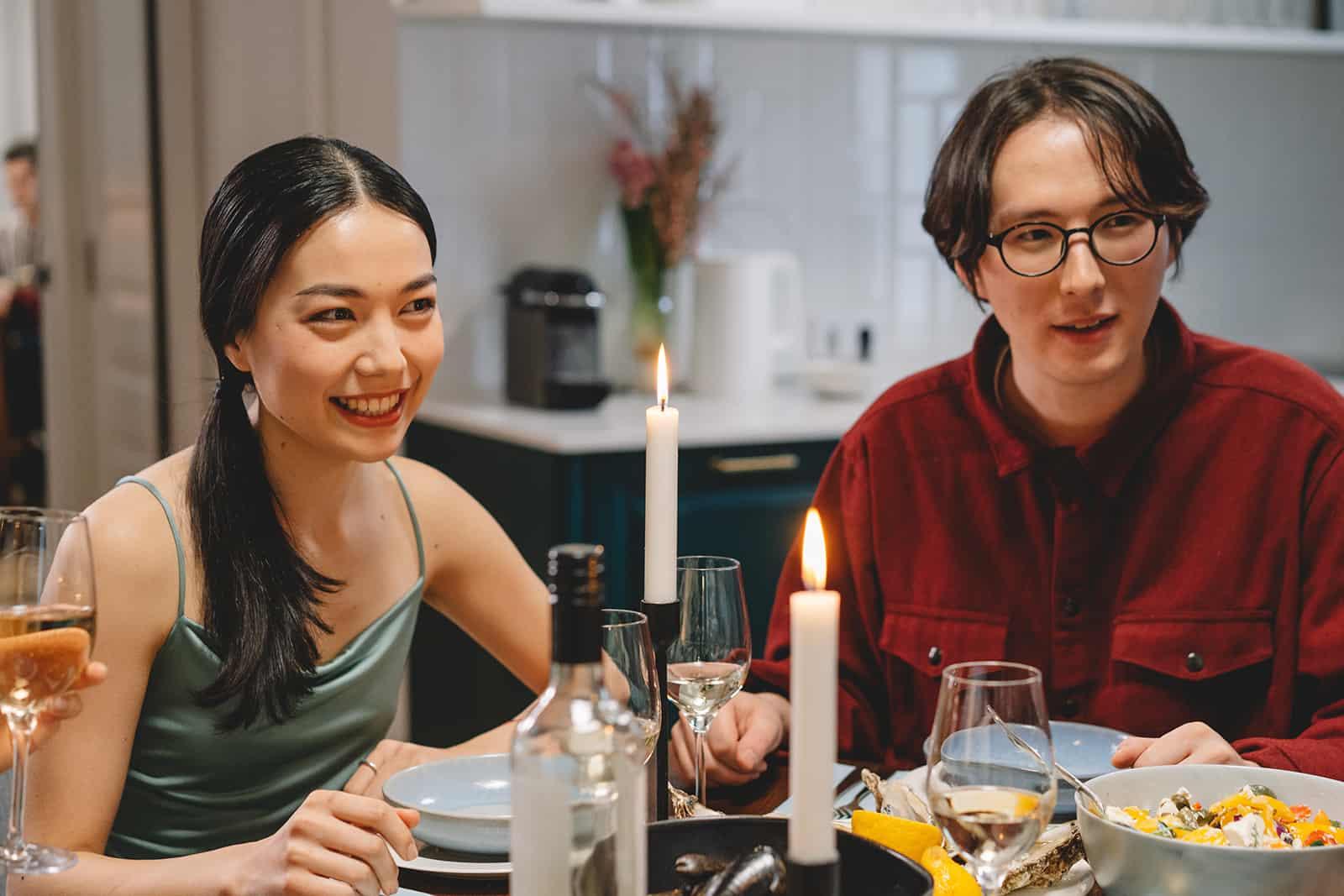 Ein Paar sitzt am Esstisch und hört Freunden zu