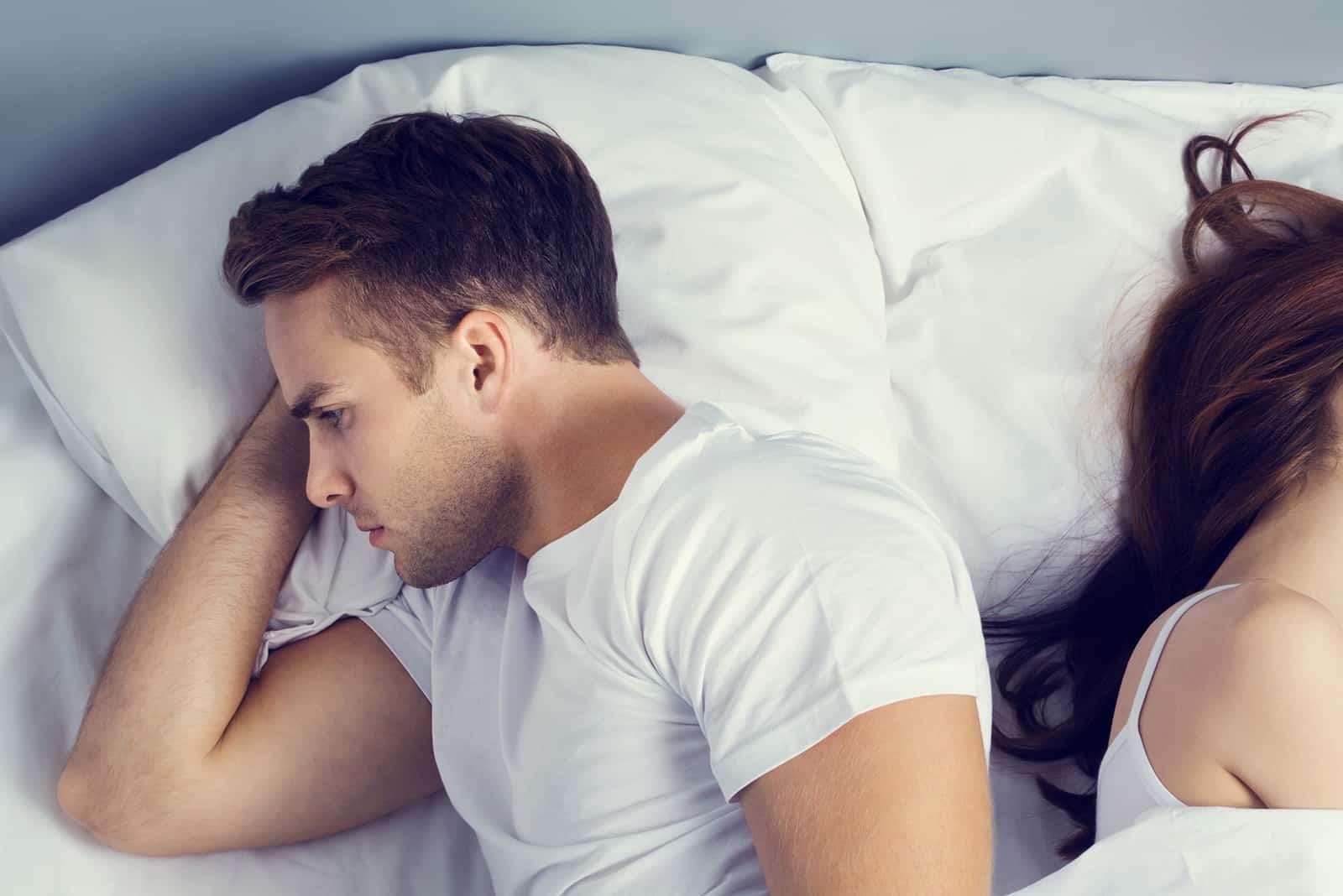 ein unglücklicher Mann, der neben seiner Freundin im Bett liegt