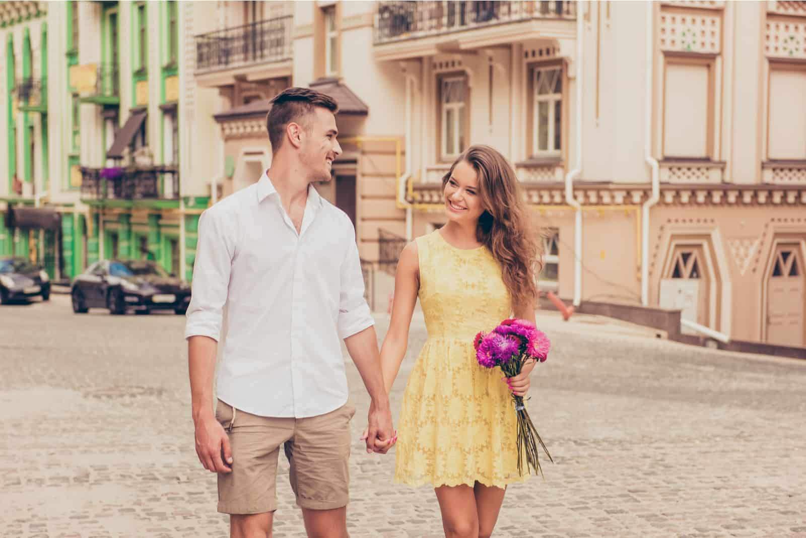ein verliebtes Paar, das Händchen haltend die Straße entlang geht