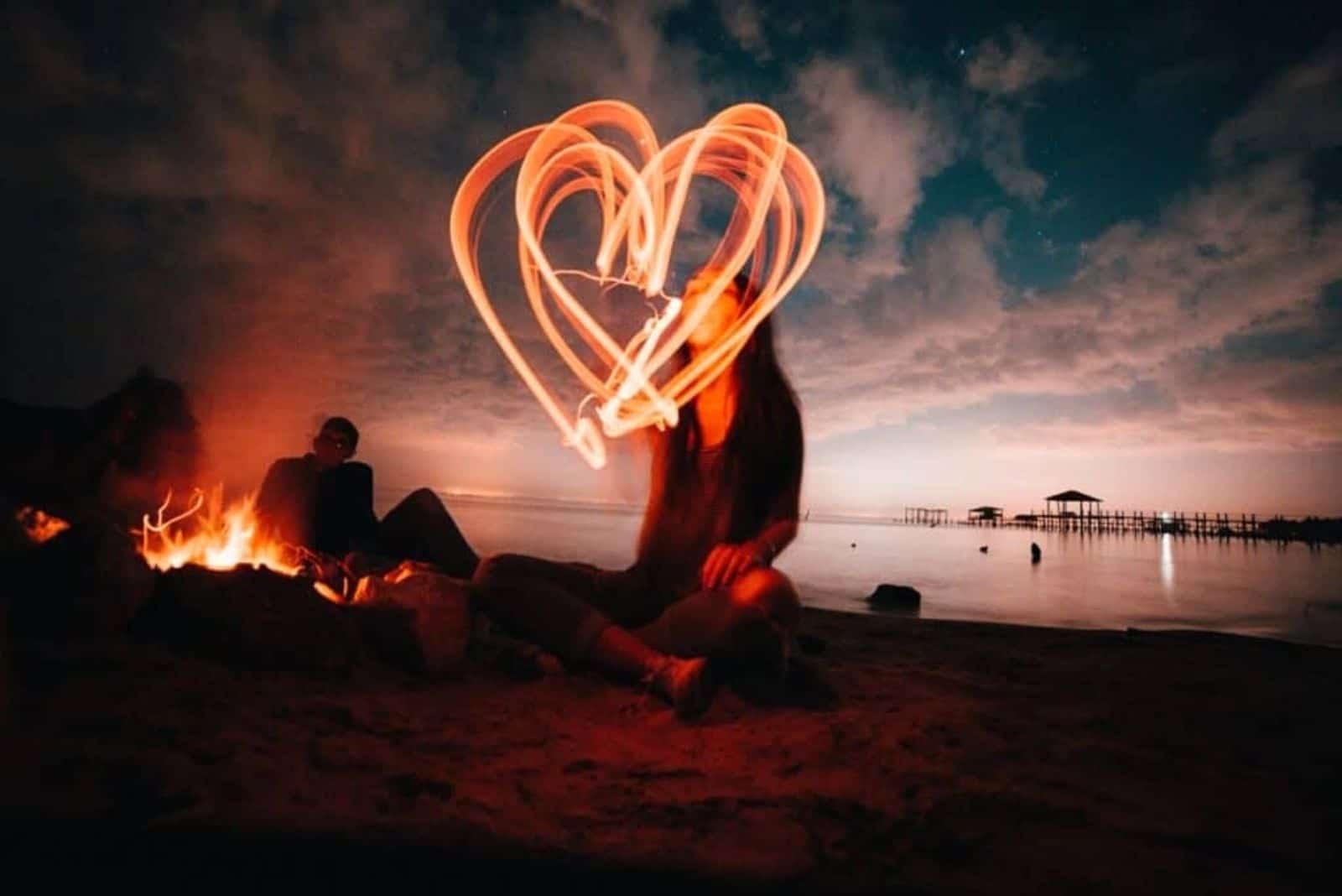 eine Frau, die abends am Strand sitzt