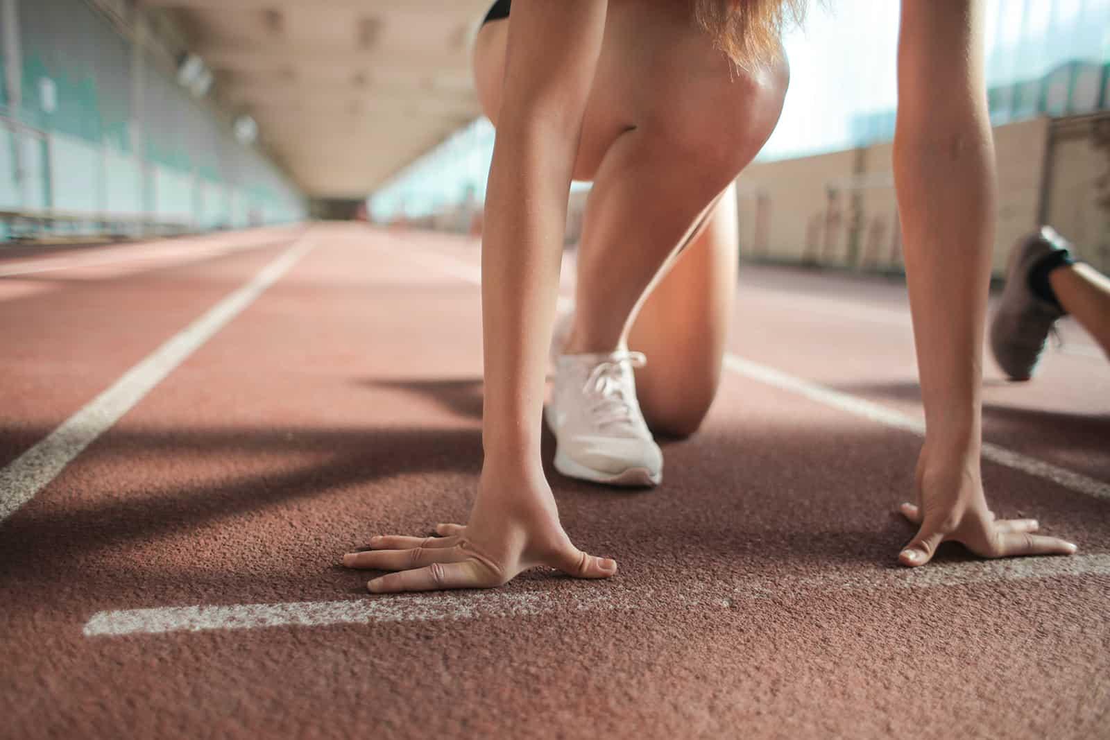 eine Frau, die auf der Startlinie steht und bereit ist, auf der Athletenbahn zu laufen