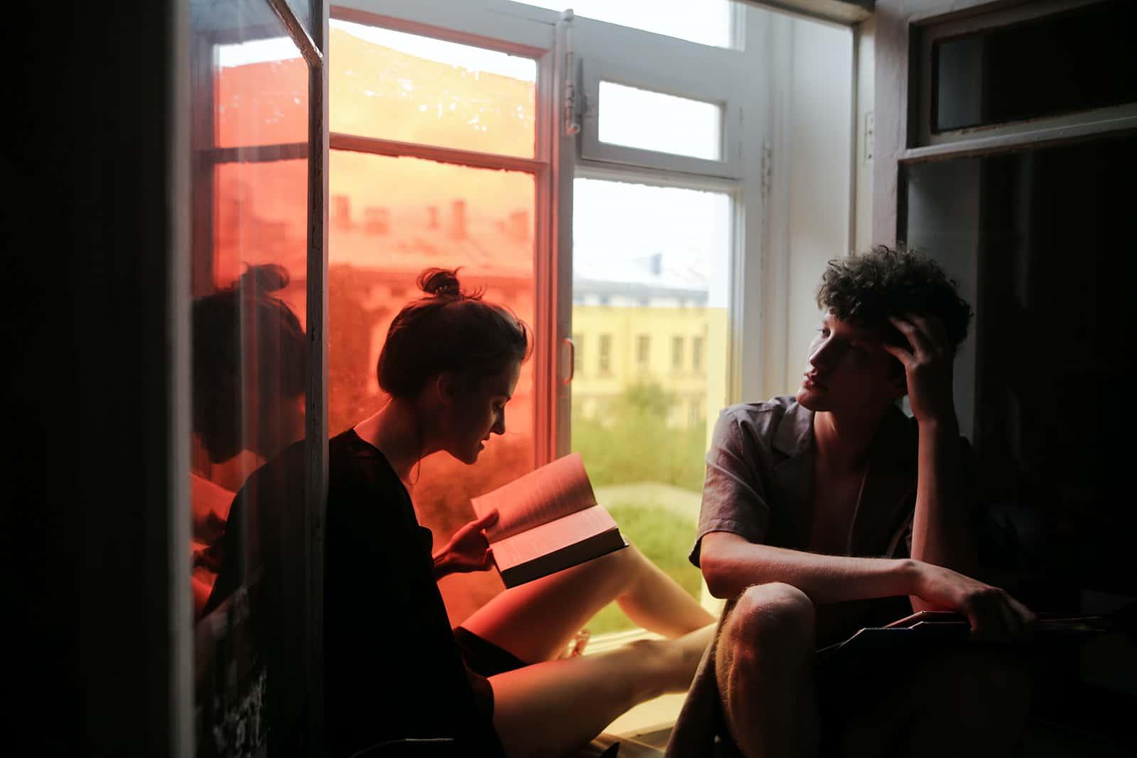 eine Frau, die einem Mann ein Buch vorliest, während sie zusammen auf einer Fensterbank sitzt