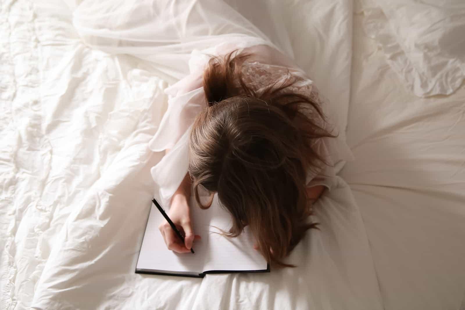 eine Frau, die einen Liebesbrief schreibt, während sie auf dem Bett liegt