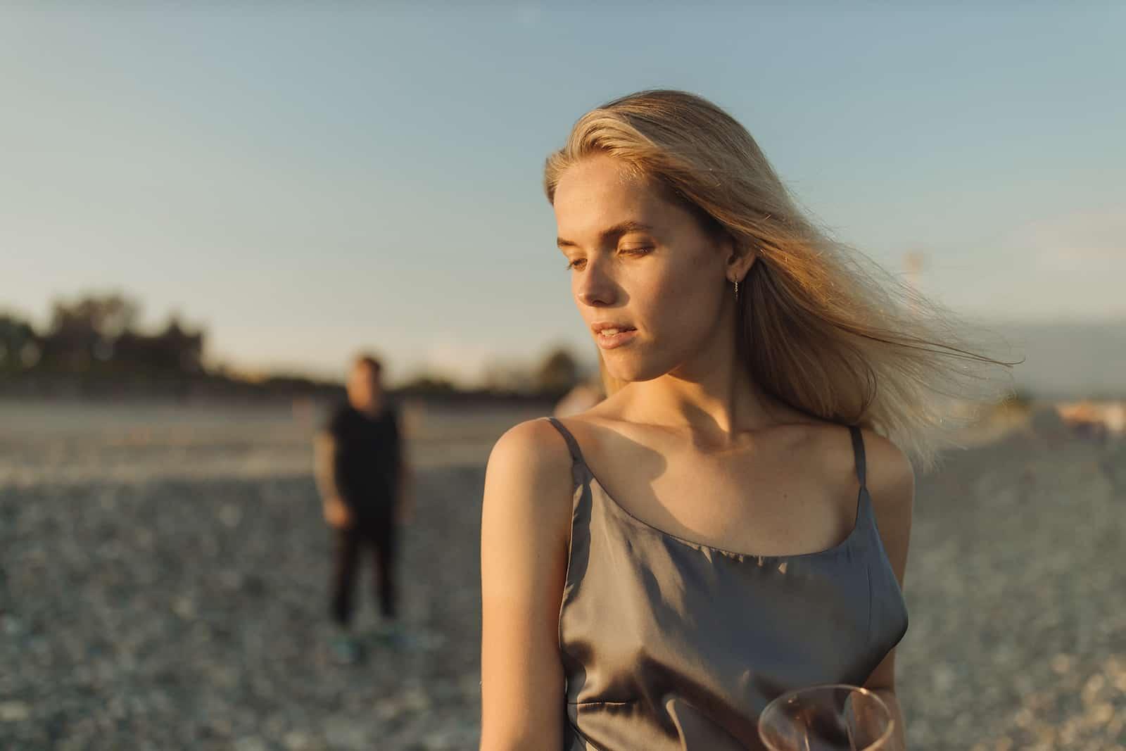 eine Frau im grauen Kleid, die vor einem Mann am Strand steht