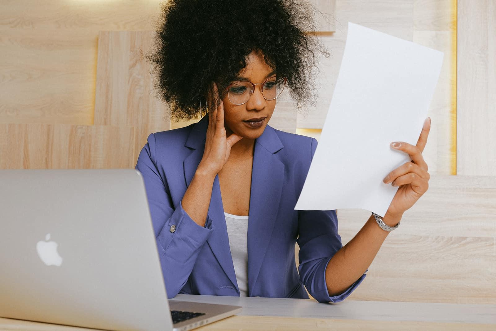 eine Geschäftsfrau, die ein Dokument im Büro liest