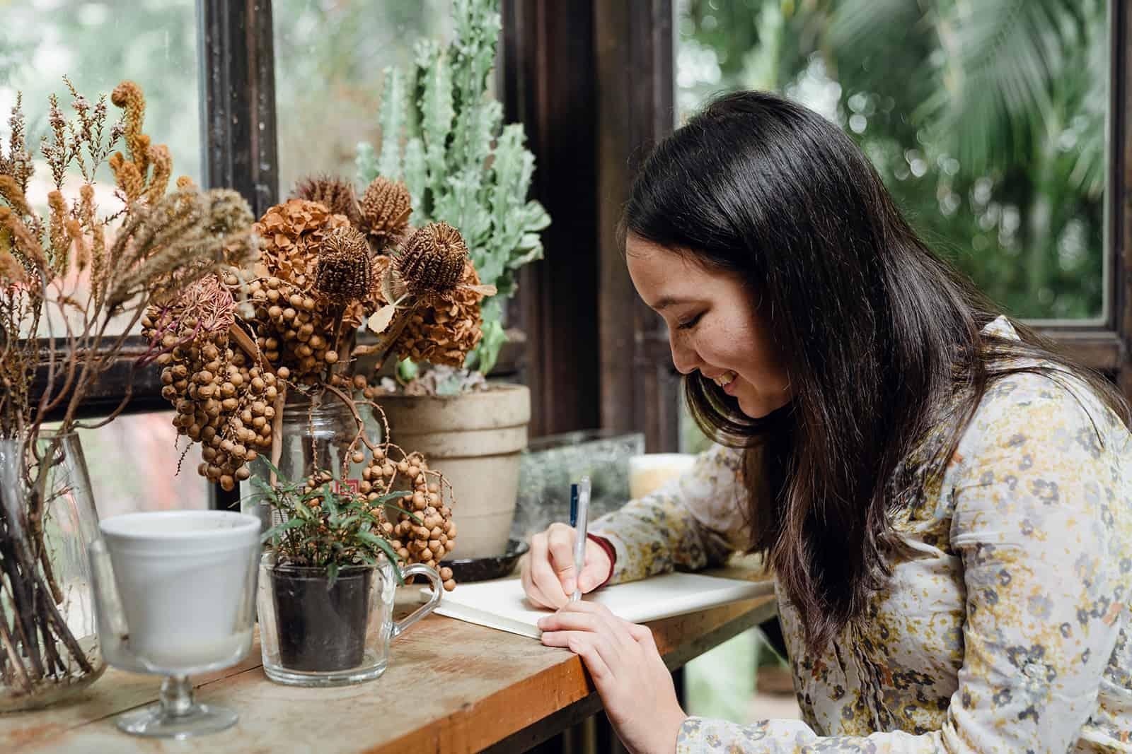 eine glückliche Frau, die einen Liebesbrief schreibt, während sie in der Nähe der Pflanzen sitzt