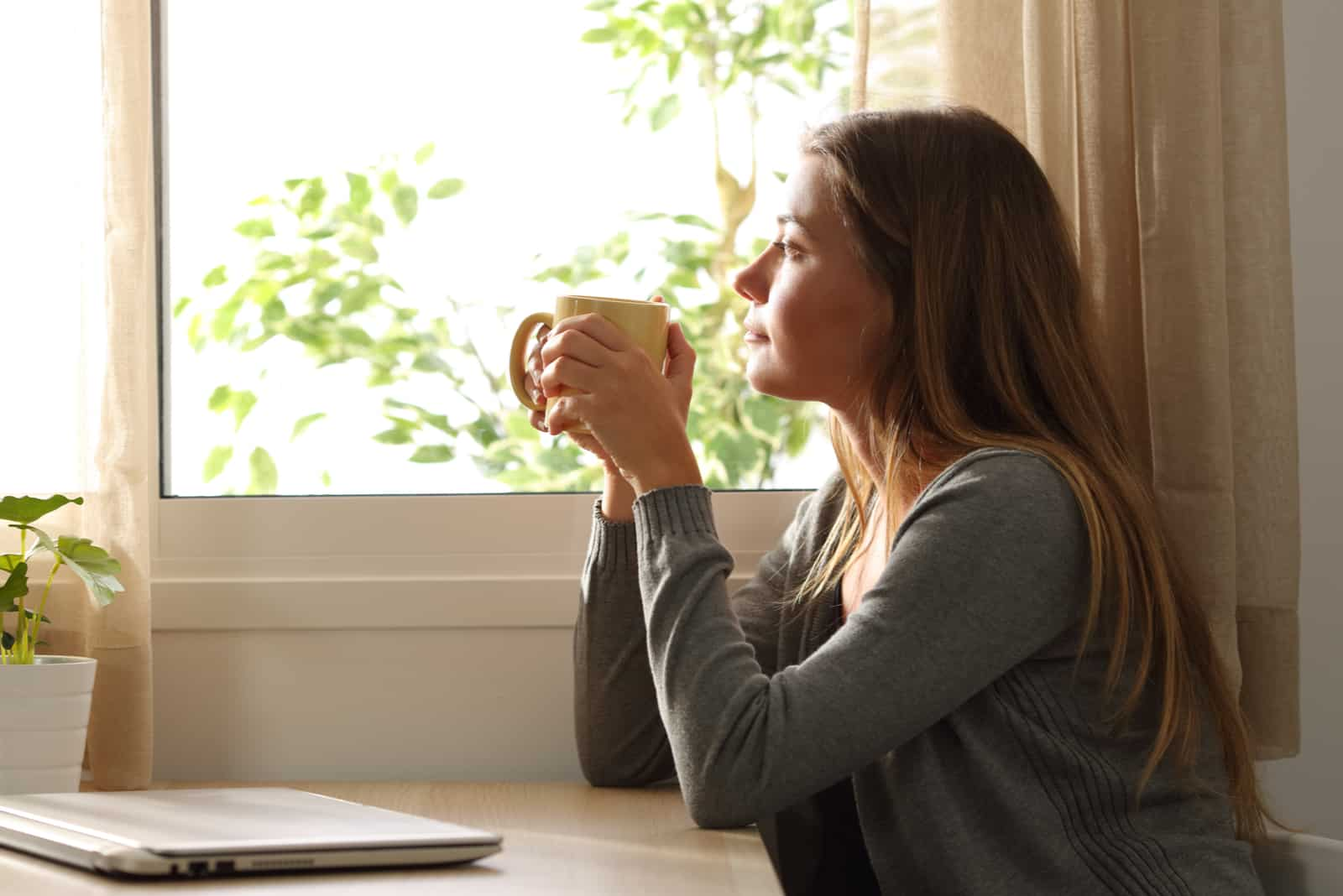 eine imaginäre Frau, die Kaffee trinkt und aus dem Fenster schaut