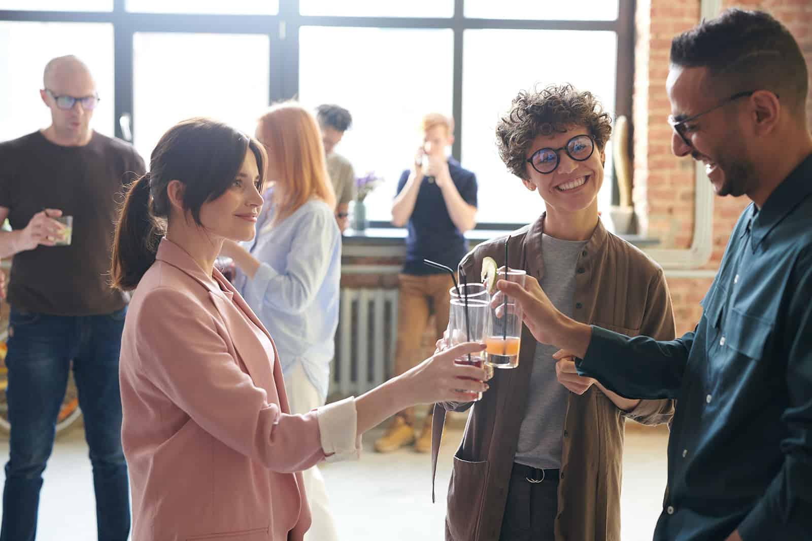 eine lächelnde Frau in rosa Blazer, die mit Kollegen auf einer Firmenfeier anstößt