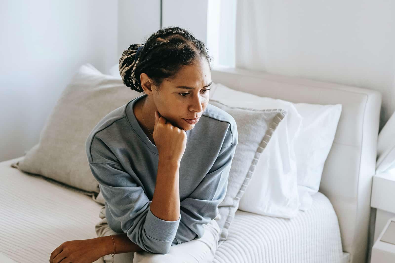 eine nachdenkliche Frau, die auf dem Bett sitzt und nach unten schaut