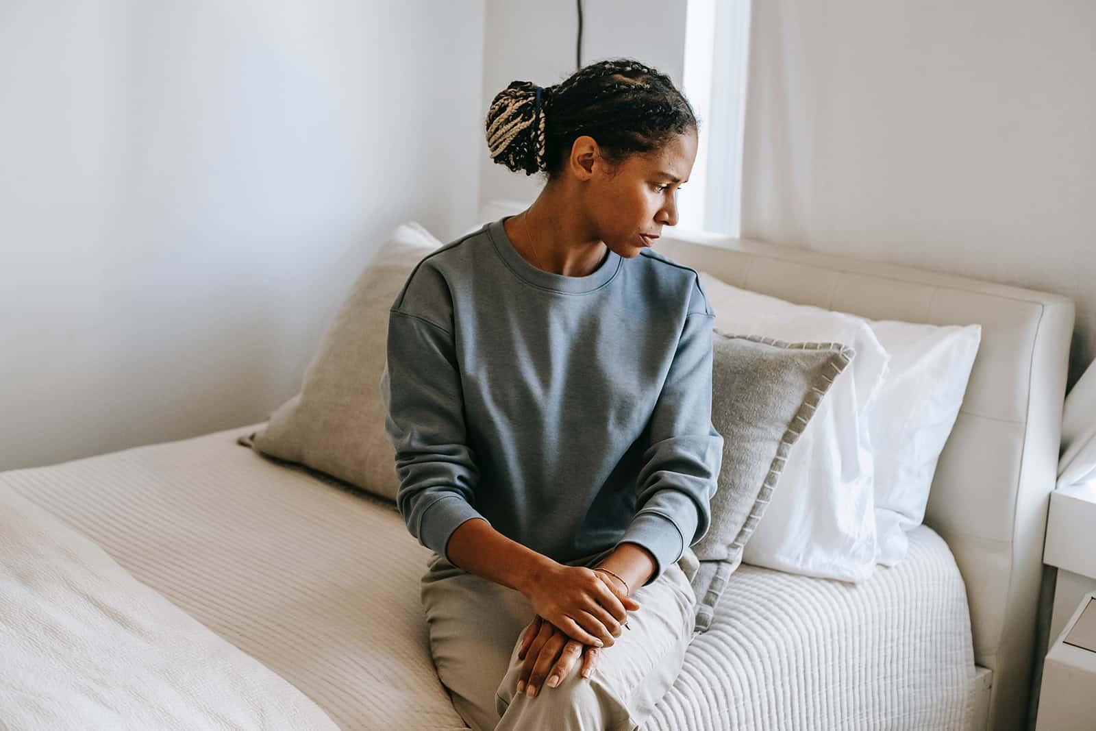 einsame Frau sitzt auf dem Bett und schaut nach unten