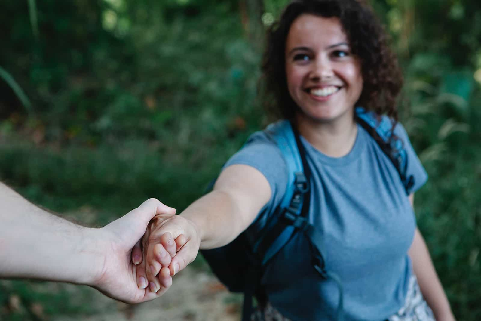 fröhliche Frau, die Hand eines Mannes beim Wandern zusammen hält