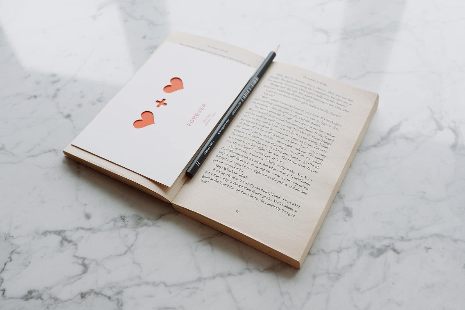 geöffnetes Buch mit Bleistift und Liebespostkarte auf Marmoroberfläche