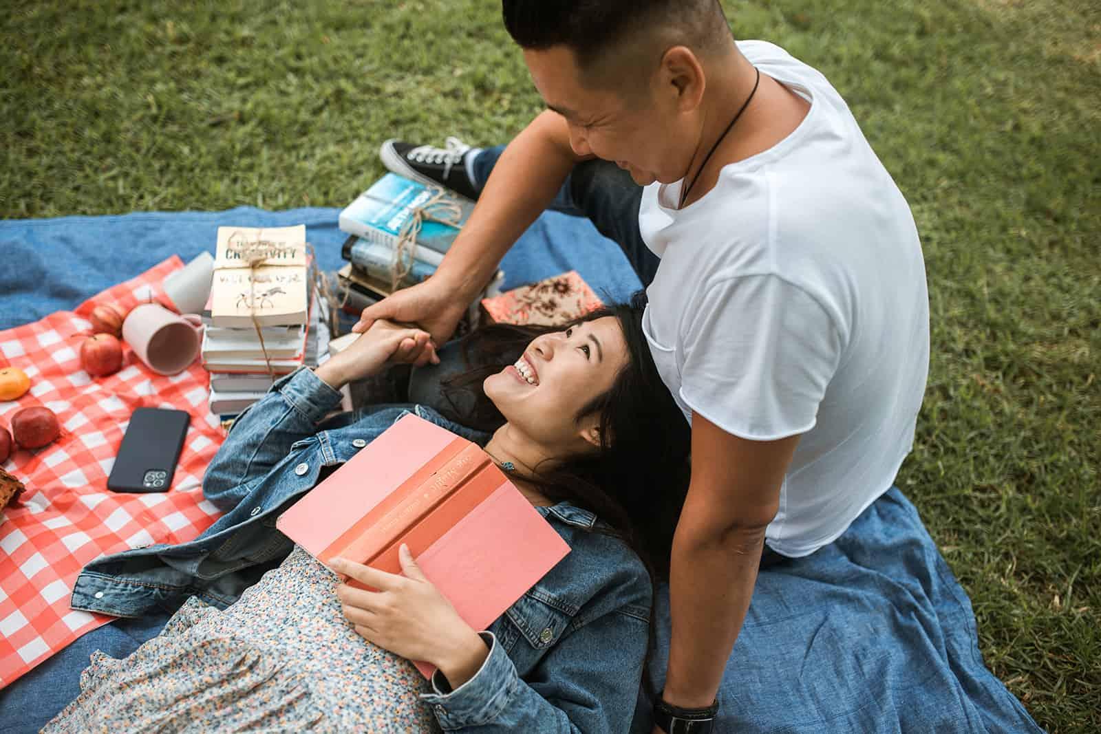 glückliche Frau, die ein Buch hält und ihren Freund beim Liegen auf der Decke beim Picknick ansieht