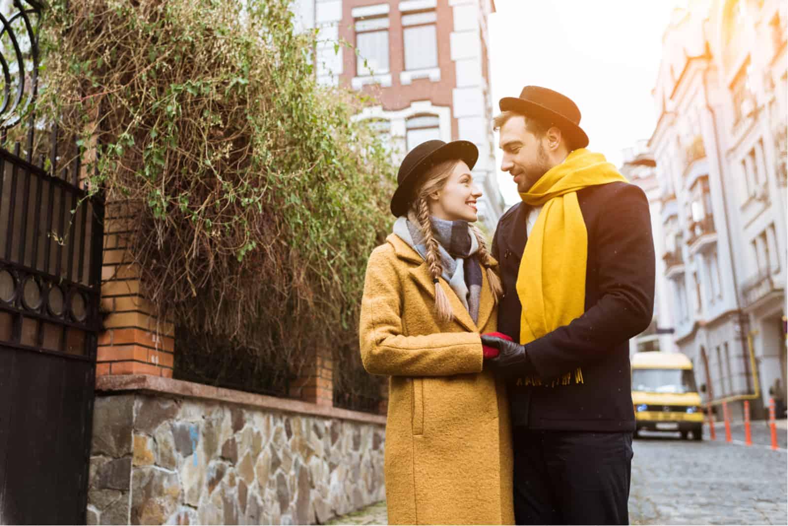 im Herbst steht ein Paar Händchen haltend auf der Straße