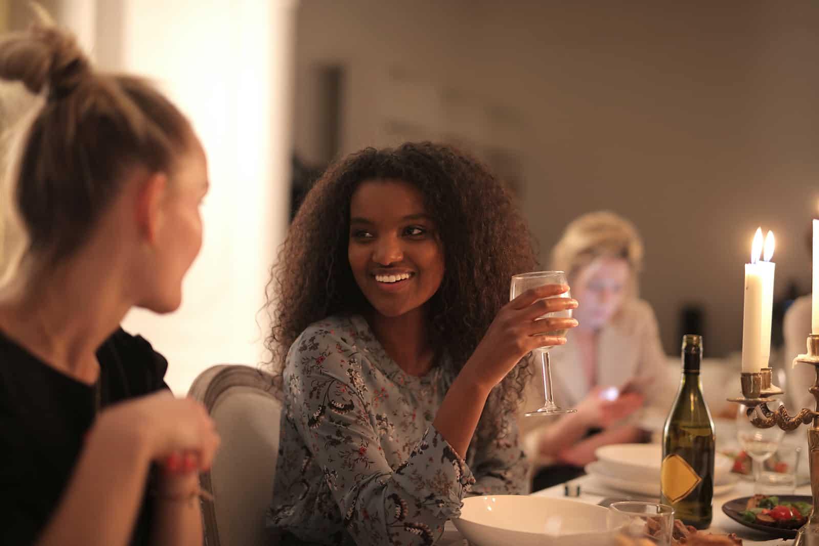 lächelnde Frau, die Wein hält und mit einer Freundin während eines Abendessens spricht