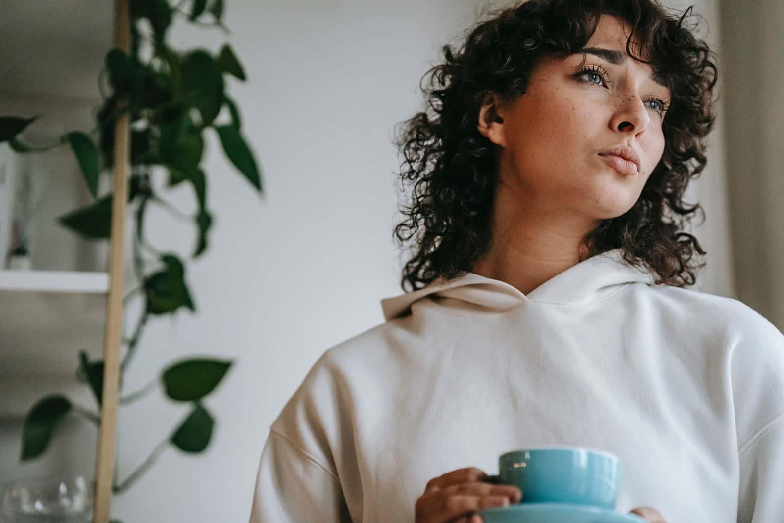 nachdenkliche Frau hält eine Tasse Kaffee und schaut zur Seite