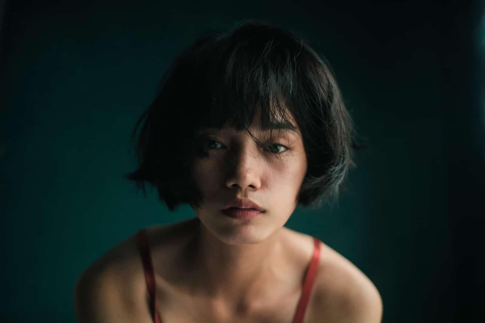 nachdenkliche Frau mit einem Bob-Haarschnitt, der nahe einer grünen Wand steht