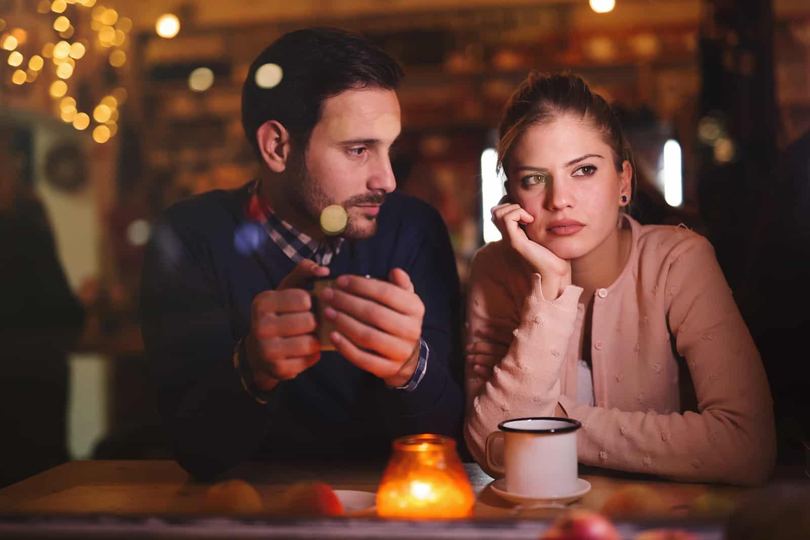 nachdenkliche Frau, die mit ihrem Freund in einem Café sitzt und zur Seite schaut
