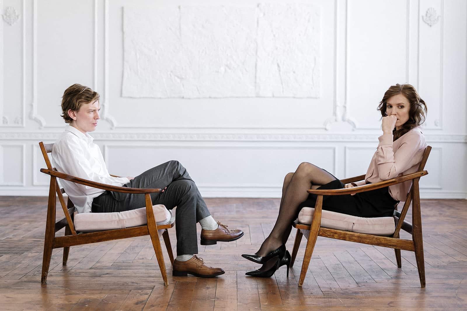 nachdenkliches Paar, das sich in den Sesseln gegenüber sitzt