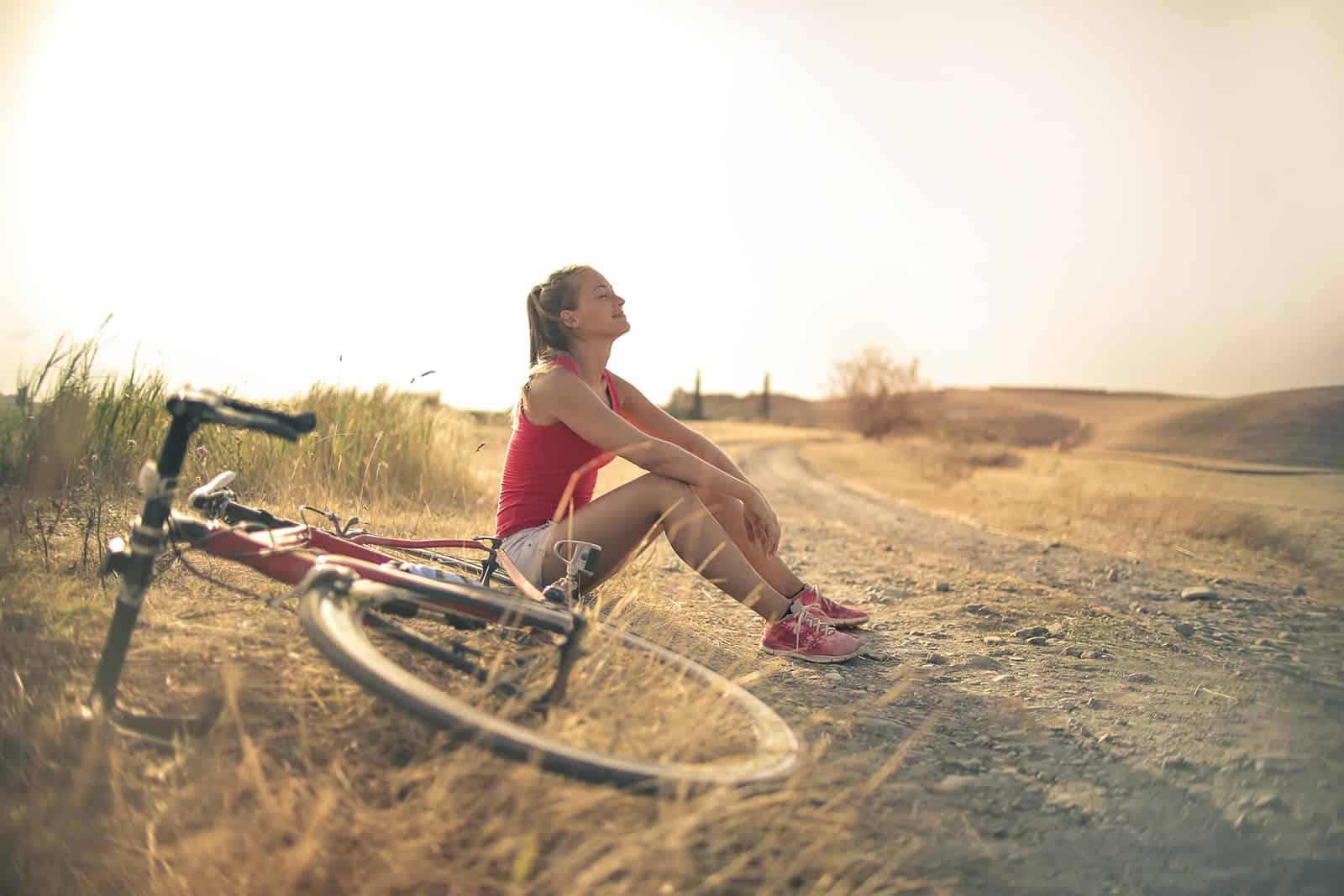 ruhige Frau, die von der Radtour ruht, die neben Landstraße sitzt