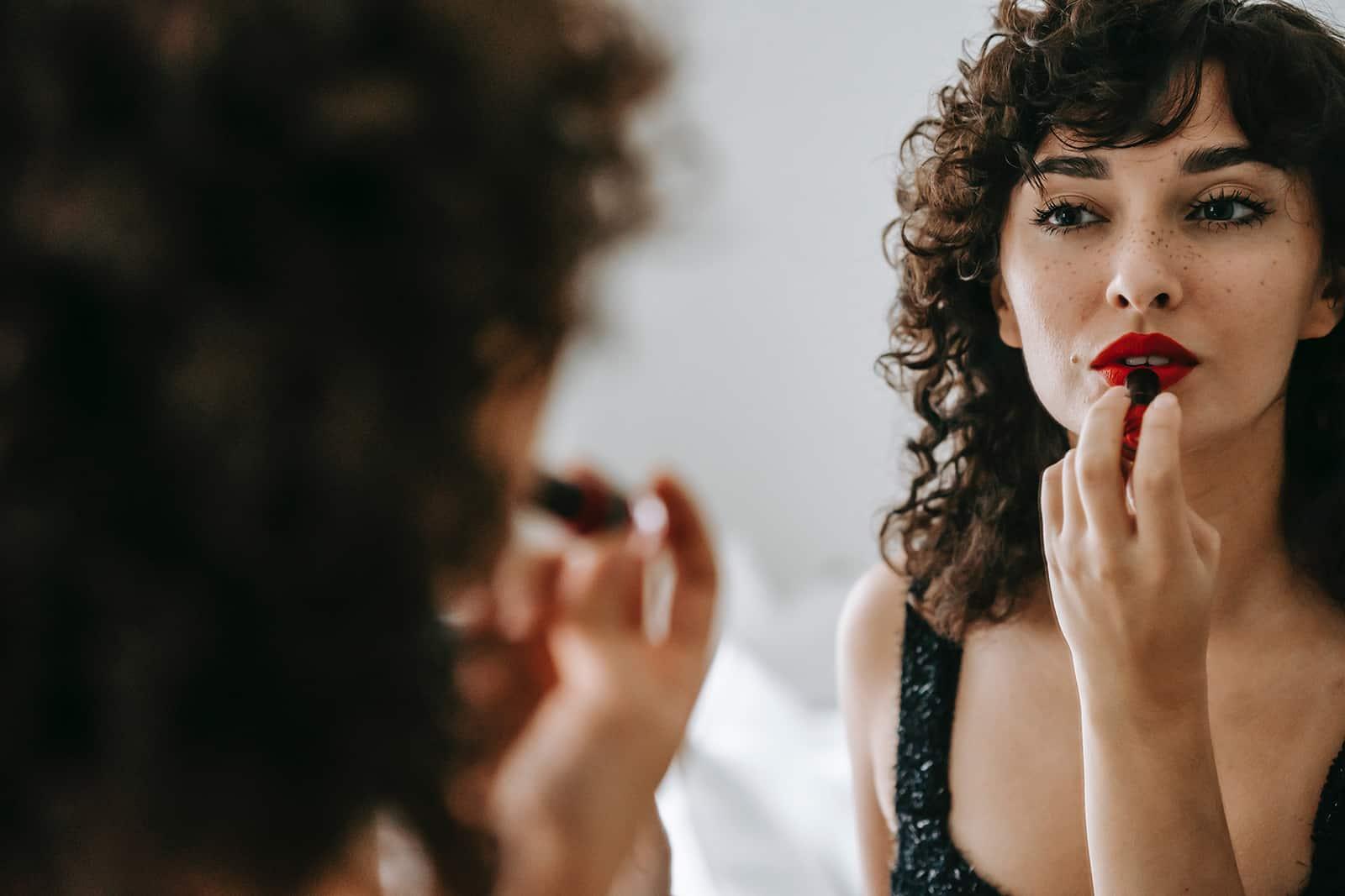 selbstbewusste Frau, die Lippenstift vor einem Spiegel aufträgt