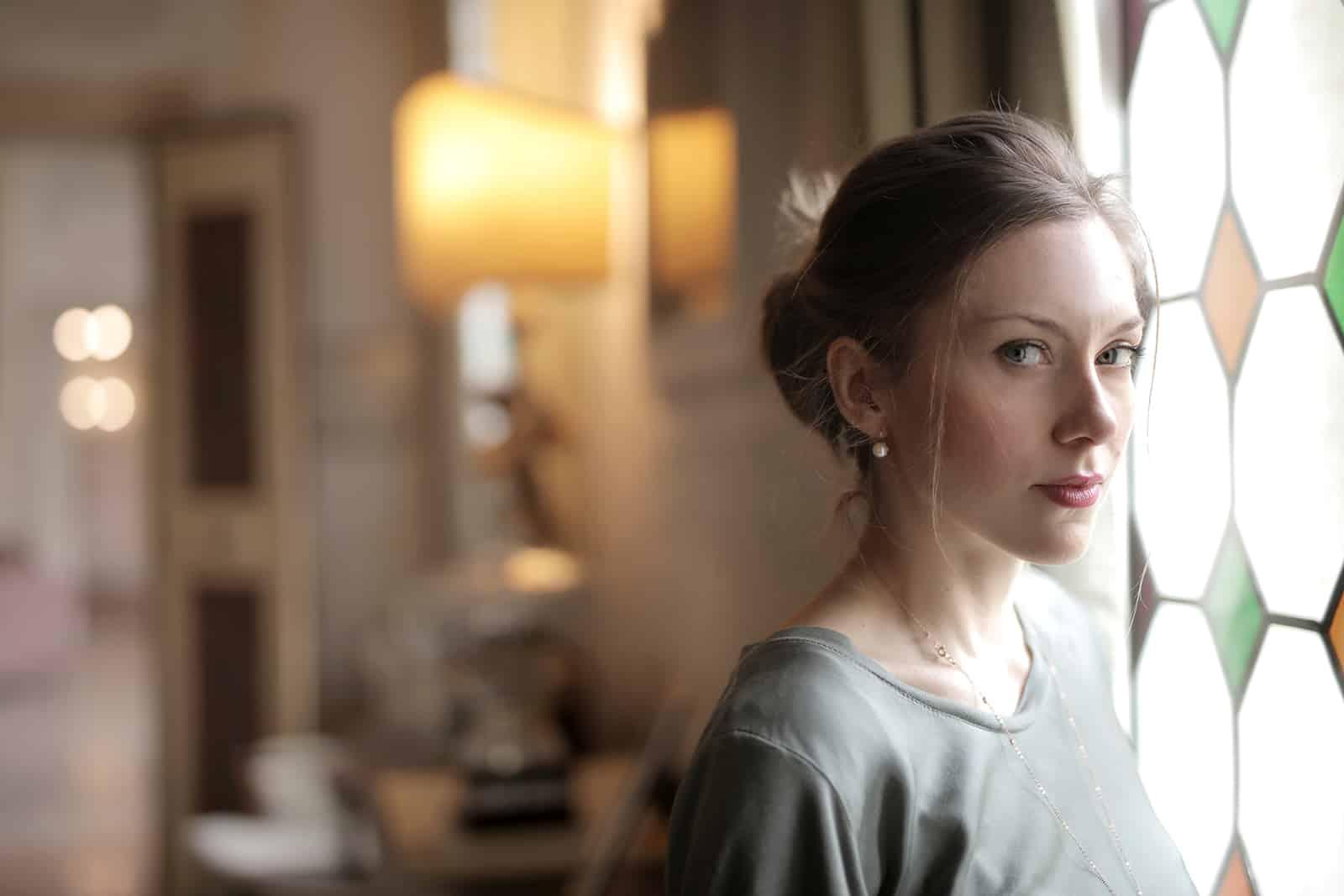 selbstbewusste Frau, die in der Nähe des Fensters im Wohnzimmer steht