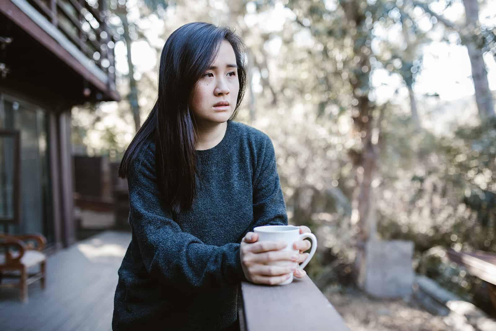 traurige Frau, die Kaffee auf der Terrasse trinkt und nachdenkt