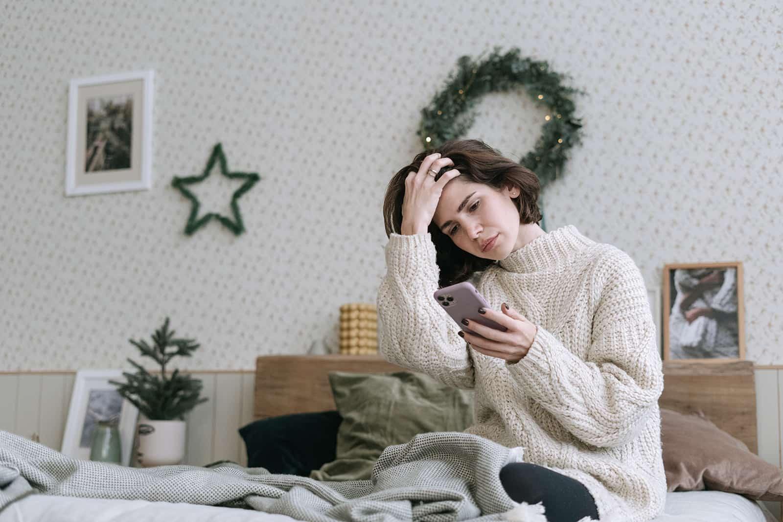 traurige Frau, die Smartphone beim Sitzen auf dem Bett betrachtet