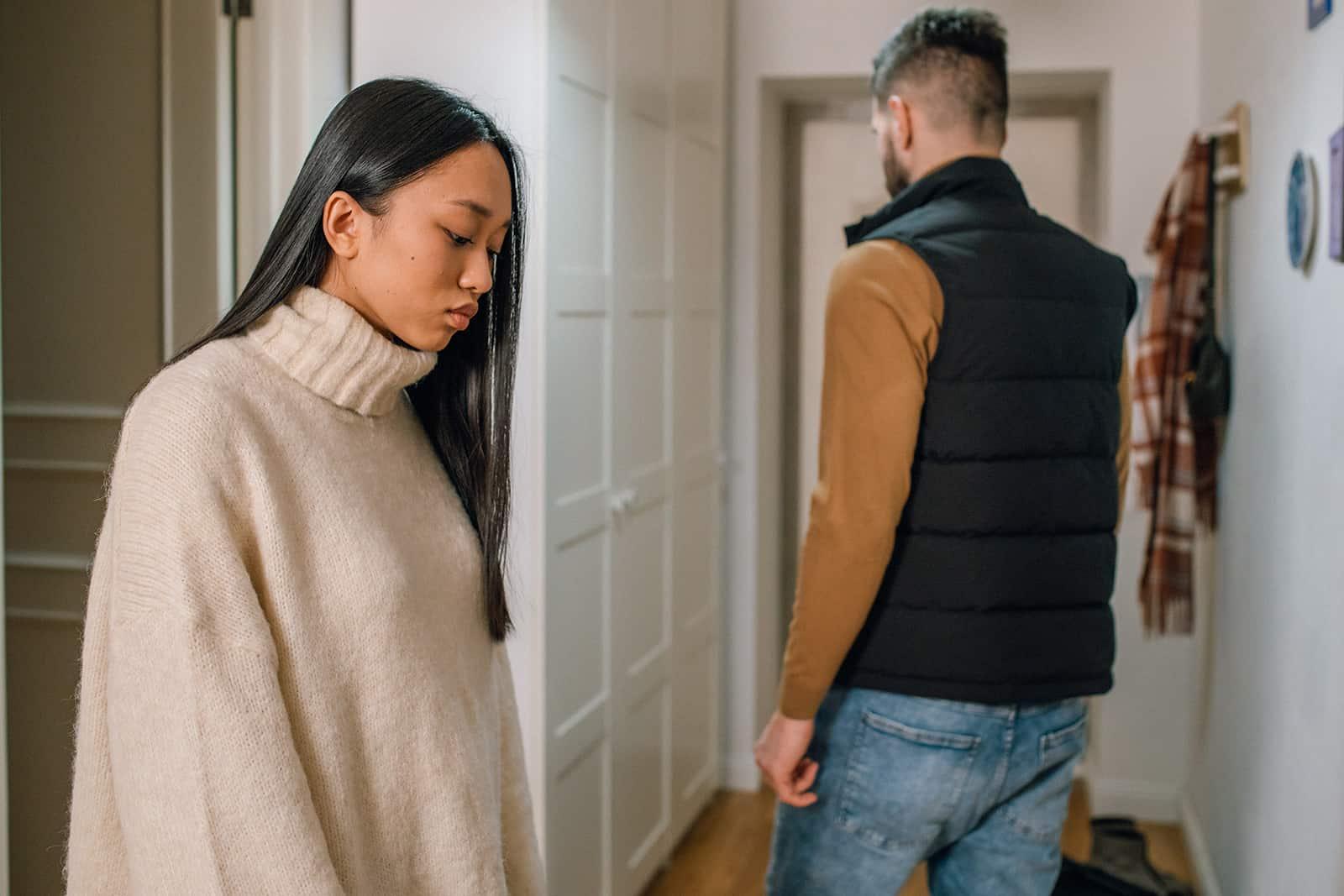 traurige Frau, die nach unten schaut, während Mann von ihr nach der Trennung verlässt