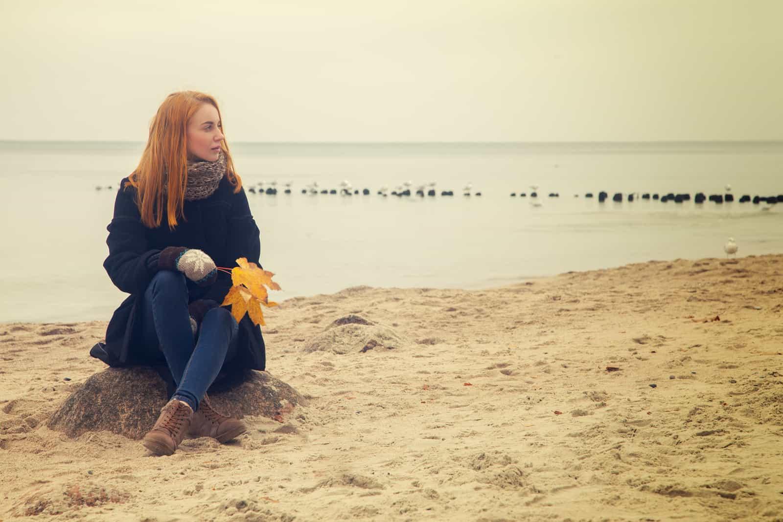 traurige nachdenkliche Frau am herbstlichen Meeresstrand sitzend