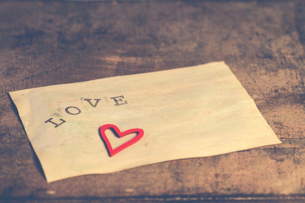 weißes Papier mit dem Wort Liebe aufgedruckt und papierförmiges Herz