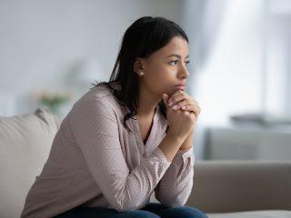 Frau sitzt auf dem Sofa im Wohnzimmer und denkt an das Problem